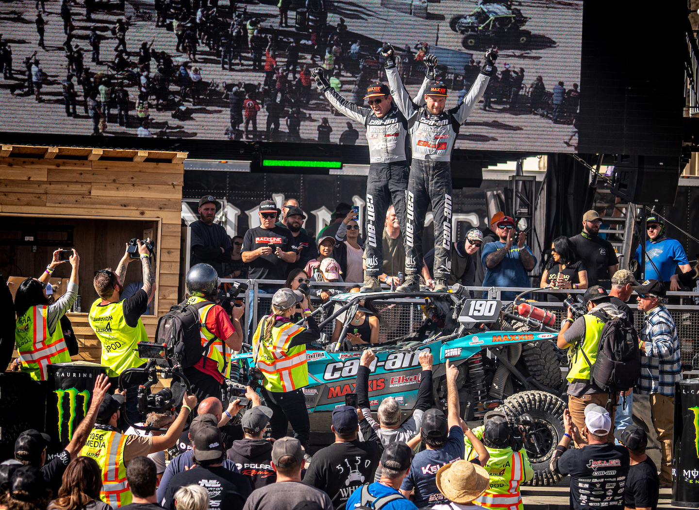 Can-Am racer Hunter Miller and co-pilot Chad Hughes celebrate on the podium after winning the 2020 Can-Am King of the Hammers UTV race in their Can-Am Maverick X3 X rc Turbo RR side-by-side vehicle.